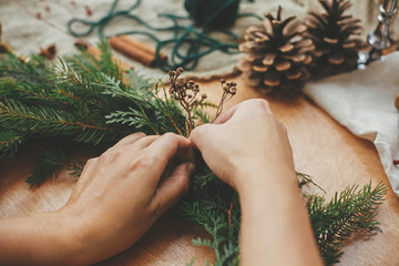 Hands holding herbs and  fir branches, pine cones, thread, berries, cinnamon on wooden table. Christmas wreath workshop. Authentic stylish still life. Making rustic Christmas wreath.