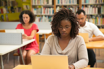 Serious African American student studying in library computer class. People sitting at desks and...