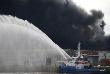 Firefighting vessel sprays water after a large fire broke out at the factory of Lubrizol in Rouen