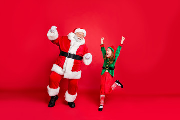 Full body photo of excited santa claus elf in hat headwear with redhead white haircut raise fists scream yes celebrate party wear green costume isolated over red background