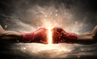Boxing fight, close up of two fists hitting each other over dark, dramatic sky with copy space
