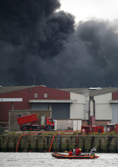 Dark smoke from a large fire that broke out at the factory of Lubrizol spreads over the town, in Rouen