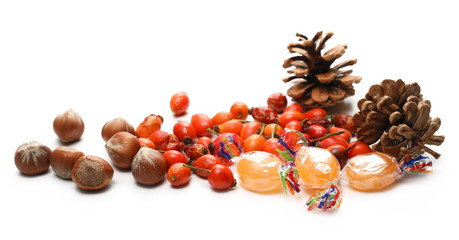 Pine cones, candies and dog rose hips Christmas ornaments, decoration isolated on white background