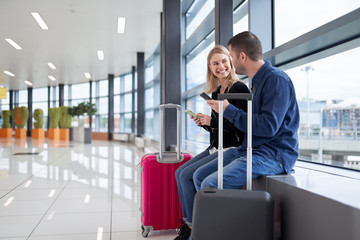 Image of man and woman with phones in their hands sitting in waiting room at airport.