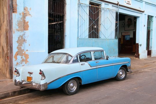 "SANTIAGO, CUBA - FEBRUARY 8, 2011: Parked classic American ""yank tank"" car in Santiago de Cuba. Cuba has one of the lowest car-per-capita rates (38 per 1000 people in 2008)."