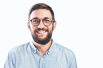 Portrait of an authentic smiling young bearded brunette man with glasses on a white background