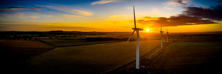 Aerial of wind turbines at sunrise in the English countryside with a dramatic sky panoramic