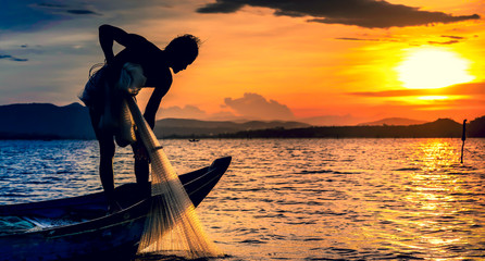 a local fisher man on boat fishing by throwing fishing net to river during sunset view .