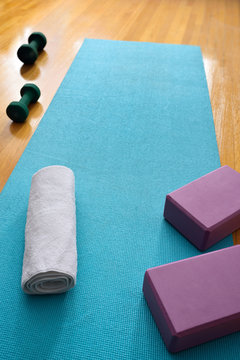 Blue yoga mat in gym studio with fresh towel and barbells and blocks