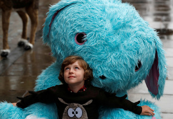 Winston Bartlett, 9, poses for a photograph with a giant Scruff-a-luvs toy at Hamleys store, ahead of announcing their top-ten Christmas toys, in London