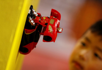 James Choung, 6, poses for a photograph with a Transforming Wall Racer at Hamleys store, after announcing their top-ten Christmas toys, in London