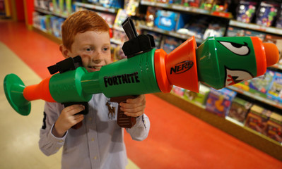 Tristan Robertson-Jeyes, 8, poses for a photograph with a Nerf Fortnite RL at Hamleys store after announcing their top-ten Christmas toys, in London