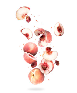 Whole and sliced fresh peaches in the air, isolated on a white background