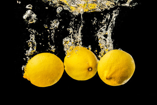 Fresh yellow lemons in water splash on black background with lots of air bubbles.