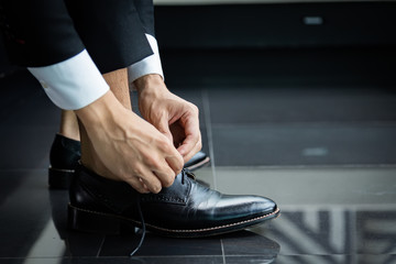 Business man in a black suit tie a black leather shoe on black floor. The hands of a business man who is shoelace.
