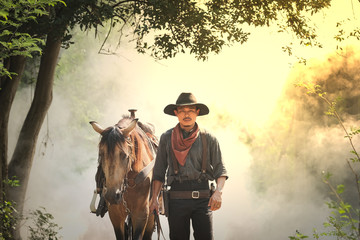 The cowboy and the horse in the morning sunrise