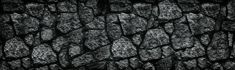 Fotobehang Stenen Natural granite stone wall wide texture. Dark rock masonry widescreen gloomy gothic background