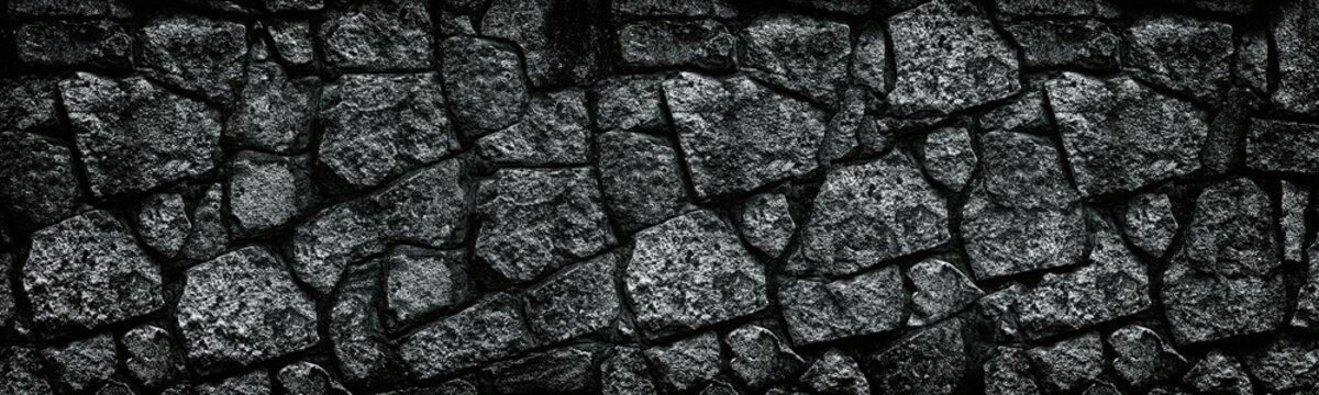 Natural granite stone wall wide texture. Dark rock masonry widescreen gloomy gothic background