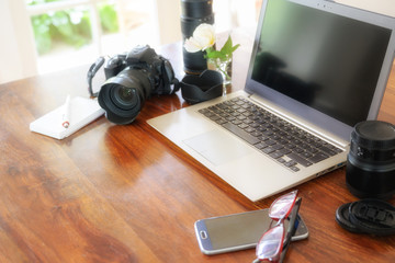workplace of a female photographer with laptop, camera and lenses on a wooden table near the window,  copy space