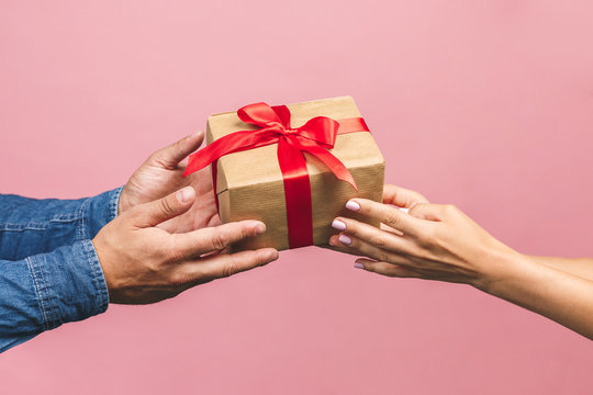Top view of male and female hands holding red gift box with golden ribbon on pink background Flat lay. Present for birthday, valentine day, Christmas, New Year. Congratulations background copy space.