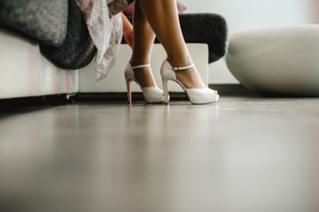 Pretty woman in lingerie putting on some high heels on her nice long legs.