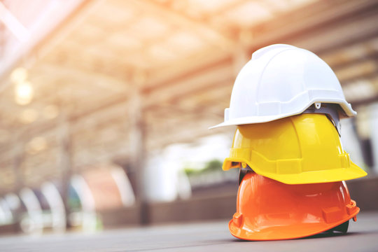 orange yellow and white hard safety wear helmet hat in the project at construction site building on concrete floor on city with sunlight. helmet for workman as engineer or worker. concept safety first