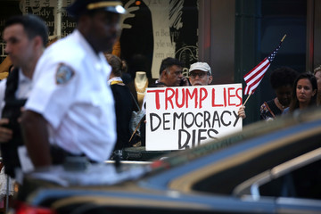 A man holds a sign outside a building where U.S. President Trump was attending a campaign fundraiser in New York