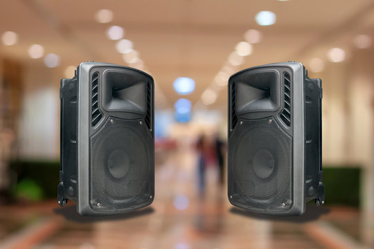 Speakers with built-in amplifiers on the concert hall background.