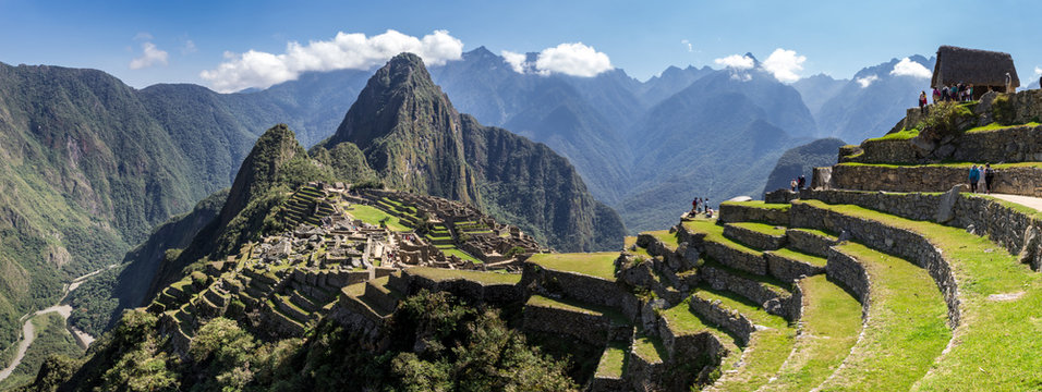 Panoramic view of Machu Picchu ruins in Peru. Behind we can appreciate big and beautiful mountains full of green vegetation. Archaeological site, UNESCO World Heritage