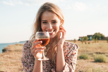 Photo of happy blonde woman holding wine glass and smiling