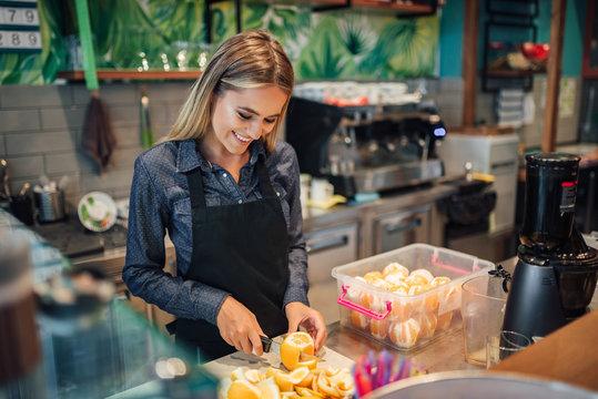 Beautiful young woman cutting lemon at small business shop.