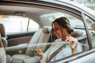 Cheerful business woman on the backseat of a car, copy space.