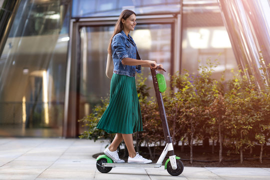Carefree young woman riding an electric scooter