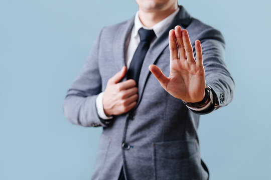 Businessman in suit making stop gesture, holding his palm outward over blue