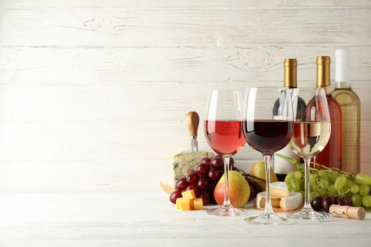 Fruits, cheese, bottles and glasses with different wine on white background, space for text
