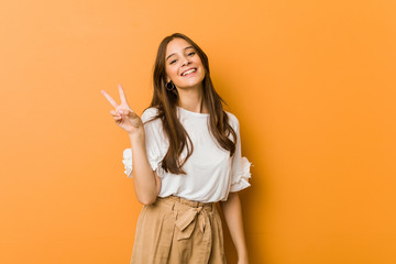 Young caucasian woman joyful and carefree showing a peace symbol with fingers.