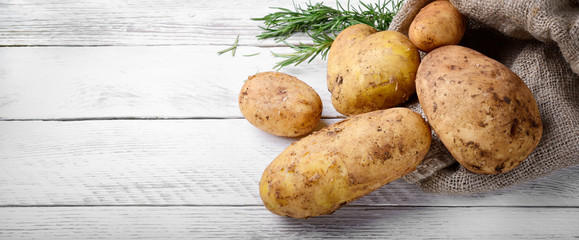 Potatoes and rosemary on white wood background. Top view, space for text