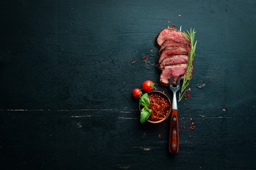 Tuinposter Steakhouse Beef steak on a fork. On a wooden background. Top view. Free space for your text.
