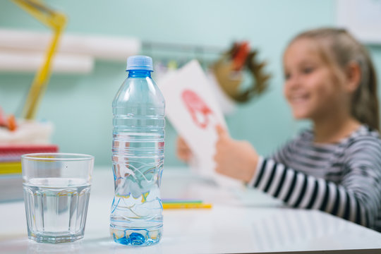 little school girl sitting desk at her room and drinking water