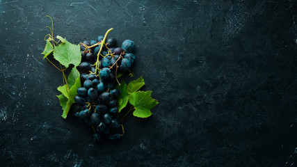Fresh red grapes with leaves on a black stone table. Top view. Free space for your text.