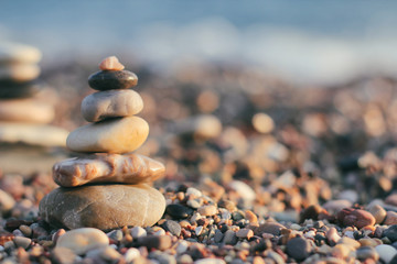 Photo sur Plexiglas Zen pierres a sable Zen pyramid of spa stones on the blurred sea background. Sand on a beach. Sea shores. Place for text. Sea view.