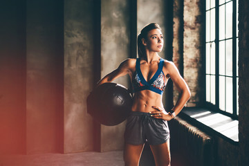Strong girl holding med ball and looking to the camera. Girl in a gym trains with the ball. Health, sport concept.
