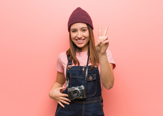 Young cute photographer woman showing number two