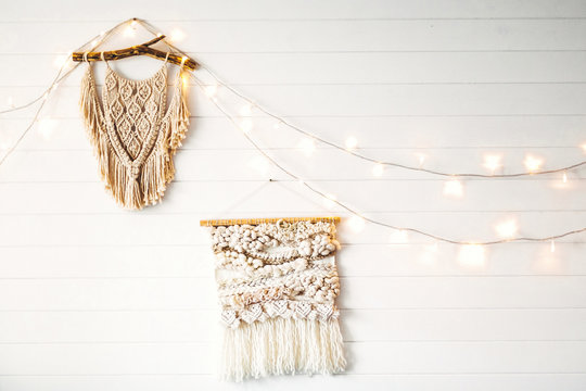 Macrame hanging on white wooden wall with lights. Stylish boho decor, modern wall hanging. Modern interior decor in scandinavian or rustic room.