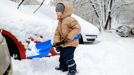 Photo of smiling boy in jacket helping to clean up the snow covered car after blizzard using big blue shovel