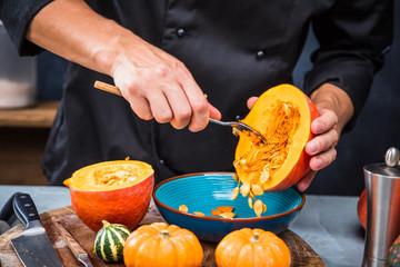 Chefkoch schneiden frische und leckere Hokkaido Kürbise  zum Kochen von Suppe
