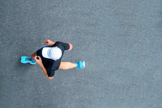 Man sprinting in the morning outdoors. Top view of male runner working out in the city.