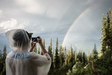 Cropped male photographing rainbow over forest through smartphone, BC