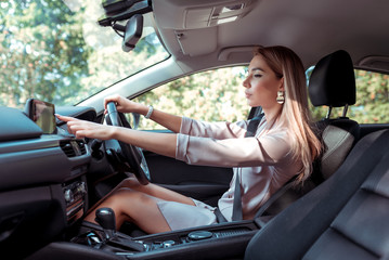 woman in pink suit in car, behind right wheel of car, selects application on touch screen display, selects route, in summer in city, business lady goes to meeting.