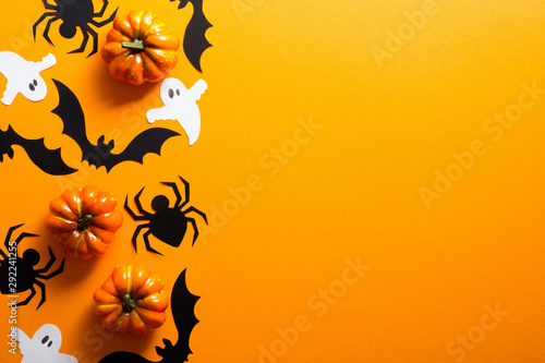 Happy halloween holiday concept. Halloween decorations, spiders, pumpkins, bats, ghosts on orange background. Halloween party greeting card mockup with copy space. Flat lay, top view, overhead.